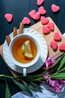 レモンスライスとソーサーにシナモンとお茶のカップと花とまな板の上のマーメラドと青の背景に布と葉の上から見る