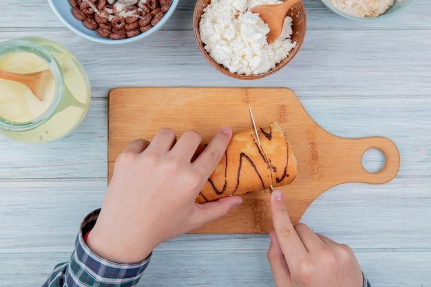 Вид сверху мужской руки режущий ролл с ножом на разделочную доску со сгущенным молоком творожные хлопья на деревянной доске