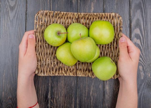 木製のテーブルに緑のリンゴがいっぱい入ったバスケットプレートを保持している男性の手の上から見る