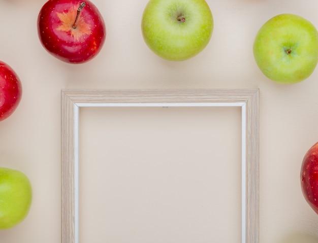 コピースペースと白い背景の上のフレームの周りのリンゴのトップビュー