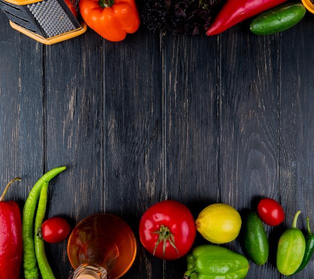 おろし金と新鮮な野菜緑唐辛子トマトキュウリのカラフルなピーマンとレモンとオリーブオイルのボトルの平面図とコピースペースと暗い木材