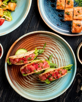 木の皿に野菜と伝統的なメキシコ料理のタコスのトップビュー