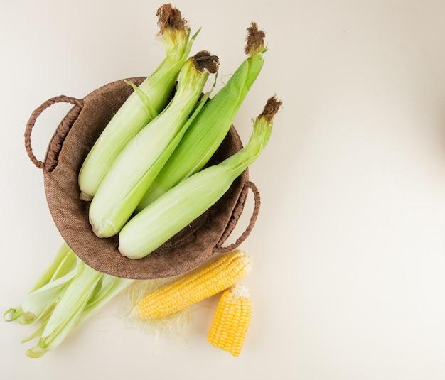 未調理のトウモロコシが付いているバスケットと調理されたトウモロコシが右側にあるトウモロコシの殻とコピースペースと白の平面図