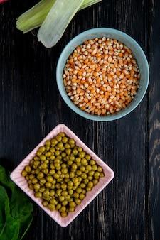 黒の乾燥したトウモロコシの種子とグリーンピースのボウルのトップビュー