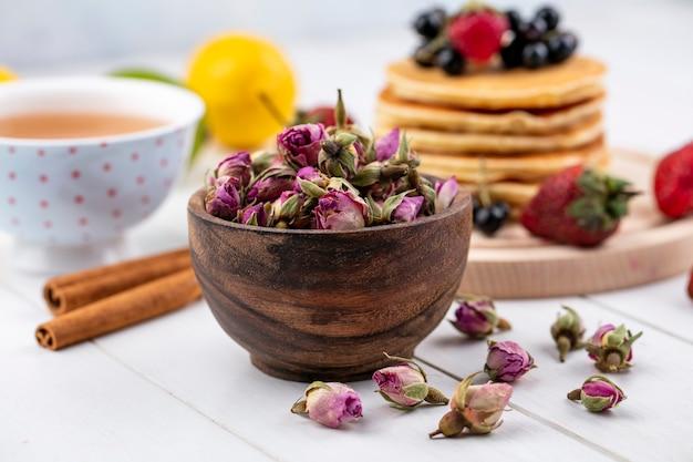 Вид спереди сушеных розовых бутонов с чашкой чая и корицей