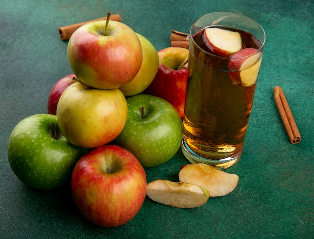 Вид сбоку цветные яблоки с корицей и стакан яблочного сока на зеленом фоне