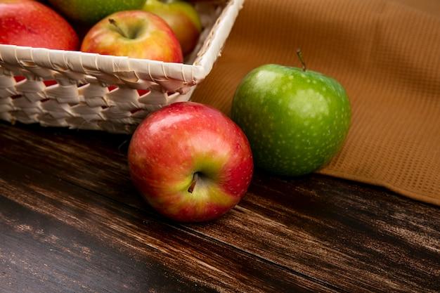 木製の背景に茶色のタオルの上にバスケットの側面図緑と赤リンゴ