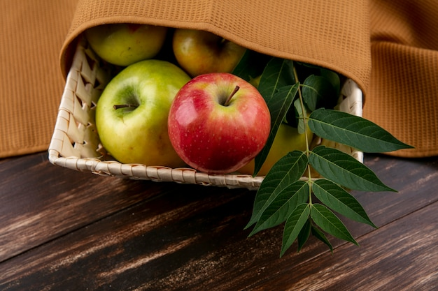 木製の背景に枝と茶色のタオルが付いているバスケットの側面図緑と赤リンゴ