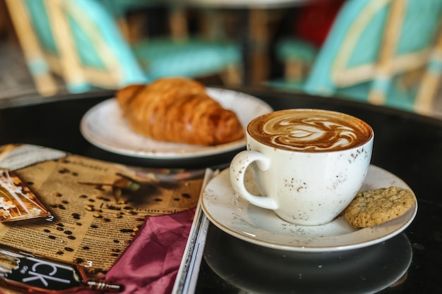 Кофе последний с печеньем круассан, вид сбоку