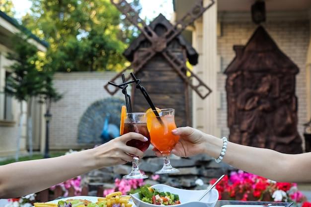 正面の女性が屋外でさわやかなカクテルをグラスにチャリンという音