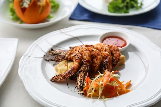 Вид спереди на гриле креветки с нарезанной морковью с соусом на тарелке