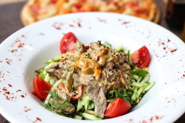 スライスしたキュウリとトマトのスパイスとプレートの正面肉サラダ