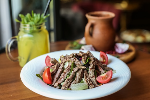 Вид спереди мясной салат с овощами и помидорами на тарелке