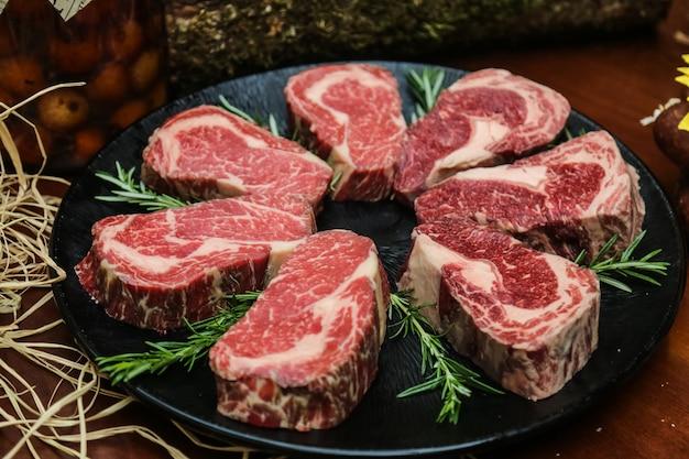 Вид спереди сырого мраморного мяса для стейка с розмарином на подставке