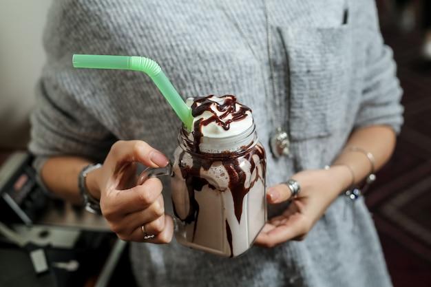 チョコレートのアイシングと緑のストローチョコレートミルクセーキを保持している正面図女性