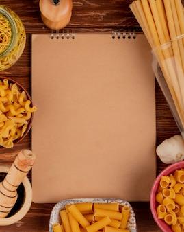 Вид сверху разных видов макарон в мисках с солью, черным перцем и чесноком с блокнотом на дереве с копией пространства