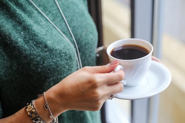 一杯のコーヒーを飲む女性の側面図