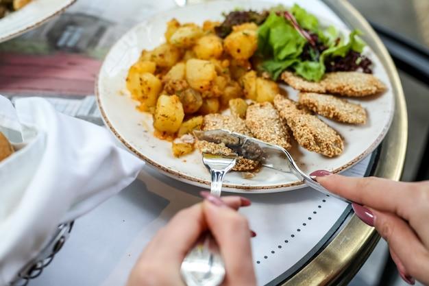 Вид сбоку женщина ест куриные наггетсы с картофелем и листьями салата на тарелке