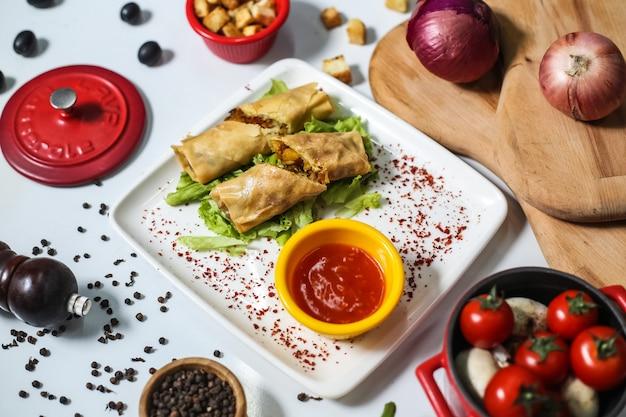 Вид сверху мясные блинчики с кетчупом на тарелку и помидоры лук и грибы на столе