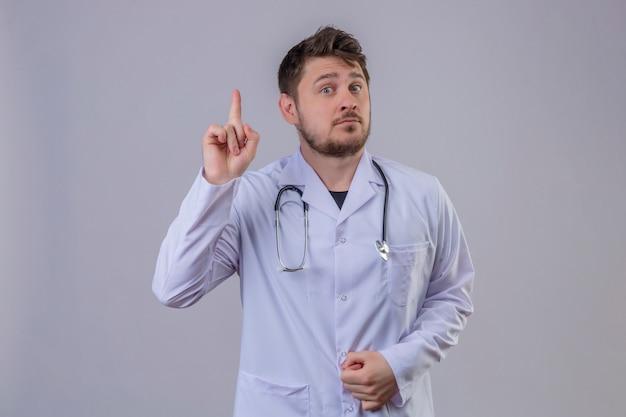 白衣と聴診器を指して、新しいアイデアコンセプトを身に着けている若い男医師