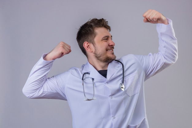 白衣と腕を上げる聴診器を身に着けている若い男医師腕力を表す上腕二頭筋、勝者の概念