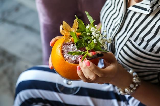 トップビューの女性は、装飾の形で花とオレンジ色のさわやかなカクテルを飲む