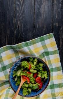 格子縞の布とコピースペースを持つ木材に野菜サラダのトップビュー