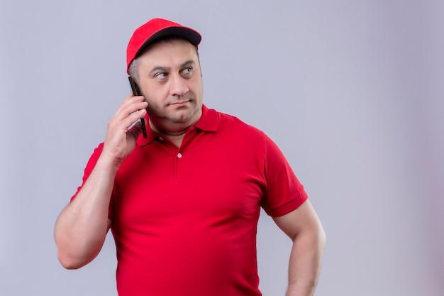 Доставка человек в красной форме и кепке разговаривает по мобильному телефону, глядя в сторону с серьезным лицом на белой стене