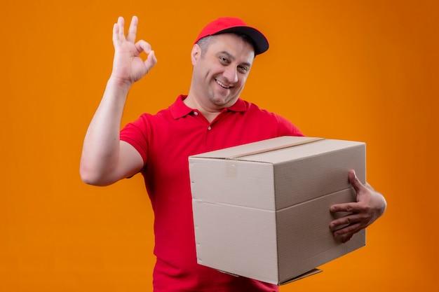 Работник службы доставки, одетый в красную униформу и кепку, держащий упаковку в коробку, смотрит положительным и счастливым, делая знак «хорошо» на оранжевой стене