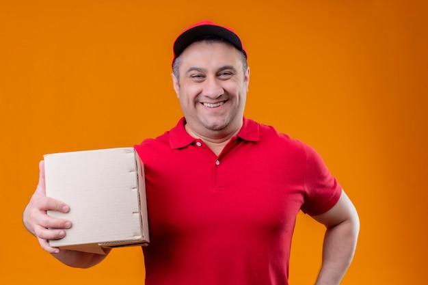 Работник службы доставки, одетый в красную униформу и кепку, держащий пакет, смотрит позитивно и счастливо, весело улыбаясь оранжевой стене