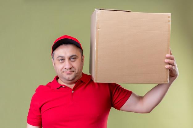 Доставка человек в красной форме и кепке держит картонную коробку на плече, глядя уверенно с улыбкой на лице