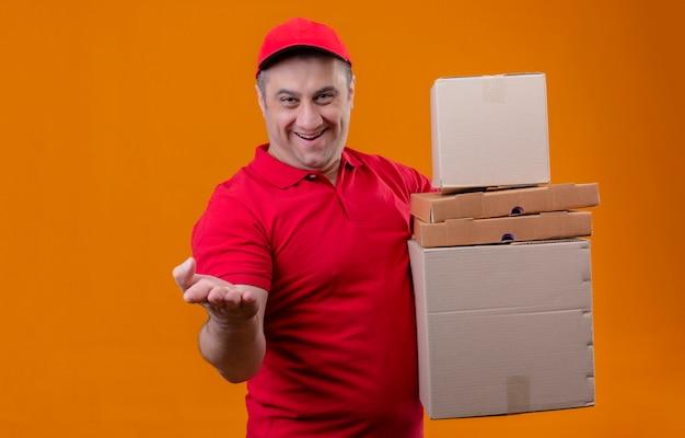 Работник службы доставки, одетый в красную форму и кепку, держит картонные коробки, смотрит позитивно и счастливо, указывая рукой на камеру над изолированной оранжевой стеной
