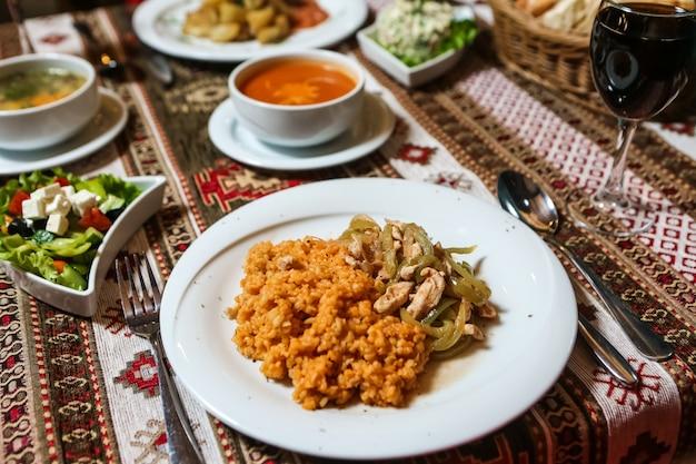 側面図フライドチキンと玉ねぎブルガーと野菜のサラダ、テーブルの上のスープ