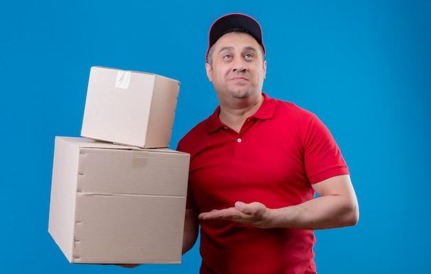 Доставка человек в красной форме и кепке держит картонные коробки, указывая на него с рукой, улыбаясь, смущенно глядя на синюю стену