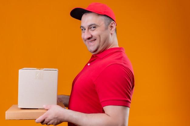 Доставка человек в красной форме и кепке держит картон сбоку, уверенно улыбаясь оранжевой стене