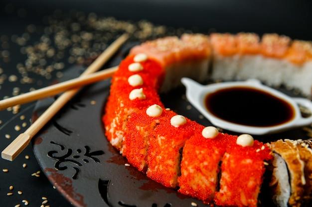 Вид сбоку филадельфия роллы с соевыми соусами и палочками на тарелке