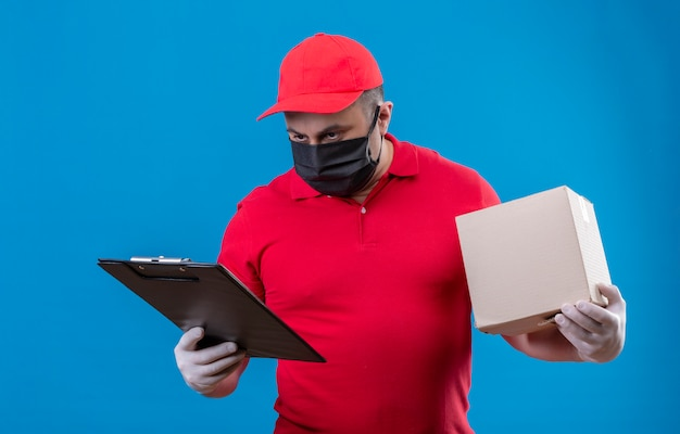 Доставка человек в красной форме и кепке в лицевой защитной маске держит картонную коробку, глядя на буфер обмена в другой руке с серьезным лицом над синей стеной
