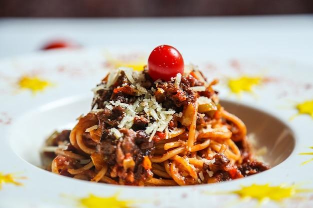 Спагетти с нарезанным мясным сыром и помидорами, вид сбоку