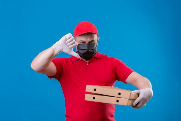 Доставка человек в красной форме и кепке в защитной маске для лица, держа коробки для пиццы, показывая большие пальцы вниз по синей стене