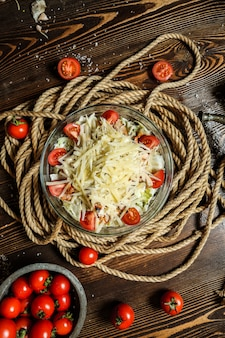 Вид сверху салат цезарь с помидорами черри в миску с веревкой на столе
