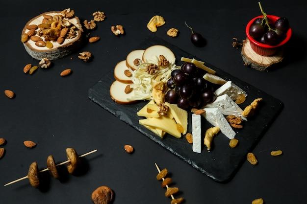 Вид сверху сырная тарелка с виноградом и орехами на подставке с сухофруктами на черном столе