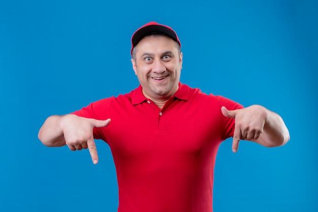 Доставка человек в красной форме и кепке, глядя удивлен и счастлив, указывая пальцами на синюю стену