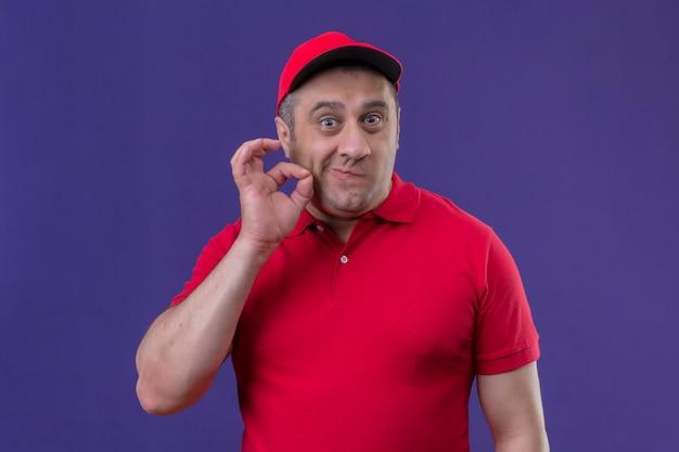赤い制服を着た配達人と紫の壁をジッパーで紙やすりで研磨して口を閉じるような手で沈黙ジェスチャーを作るキャップ