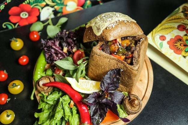 Вид сверху на гриле мясо с овощами в булке из серого хлеба с помидорами черри, грибами и зеленью с базиликом на подставке