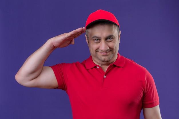 Счастливый доставщик в красной форме и кепке, делая салют готов к работе, улыбаясь дружелюбно над изолированных фиолетовые стены