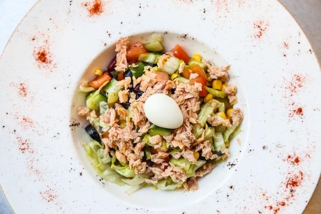 Вид сверху салат из тунца с вареным яйцом на тарелке