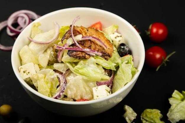 フライドチキンのクローズアップビューと野菜のサラダ