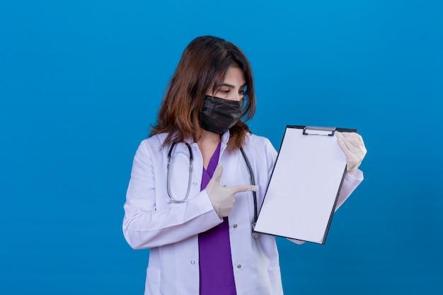Доктор средних лет в белом халате в черной защитной маске для лица и со стетоскопом, держащим буфер обмена