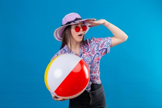青い壁を越えて誰かを探している手で遠く離れているインフレータブルボールを保持している赤いサングラスをかけている夏帽子の若い女性