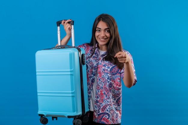 青い壁を越えてカメラに人差し指で明るく指している陽気で幸せな笑顔を探している青いスーツケースを持った若い美しい旅行者女性